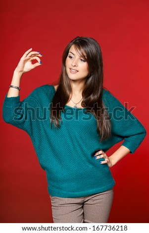 Woman in warm clothes with thumb and forefinger together simulating holding or picking something up - stock photo