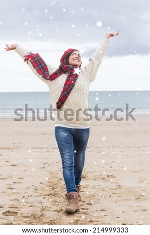Woman in warm clothing stretching her arms at beach against night sky