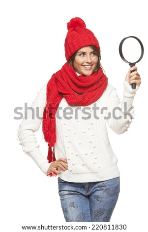 Woman in warm red winter hat and scarf looking through the magnifying glass at blank copy space, over white - stock photo