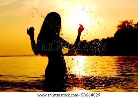 woman in water outdoor sunrise splash - stock photo