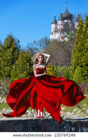 Woman in waving dress with flying fabric on forest background - stock photo