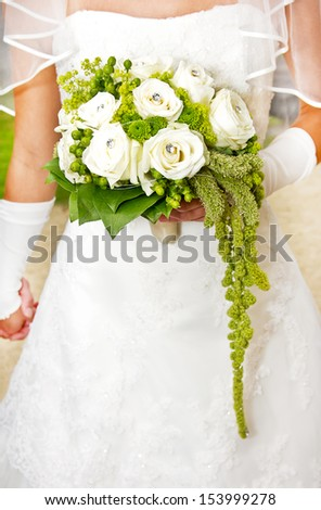 woman in wedding dress holding a wedding bouquet - stock photo