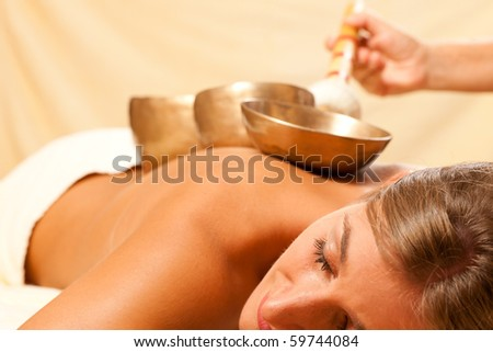 Woman in wellness and spa setting having a singing bowl therapy session