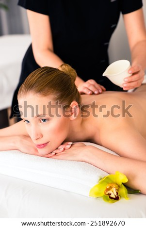 Woman in wellness beauty spa having back massage with essential oil, looking relaxed - stock photo