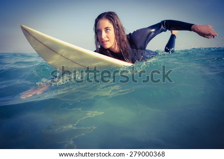 woman in wetsuit surfing on sunny day - stock photo