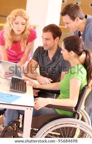Woman in wheelchair attending group meeting - stock photo