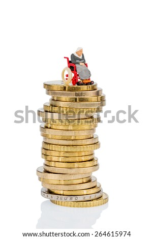 woman in wheelchair on money stack symbol photo for care allowance, health care costs - stock photo