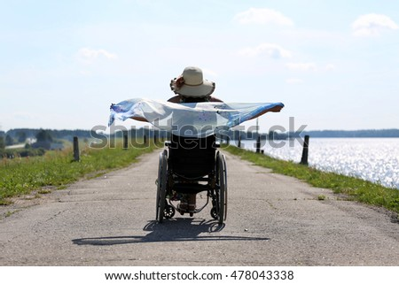 Woman in wheelchair outdoor walking near sea - disability and lifestyle