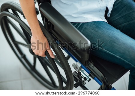 Woman in wheelchair's hand on wheel close up, disability and handicap concept - stock photo