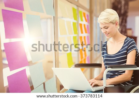 Woman in wheelchair using computer against colorful adhesive notes - stock photo