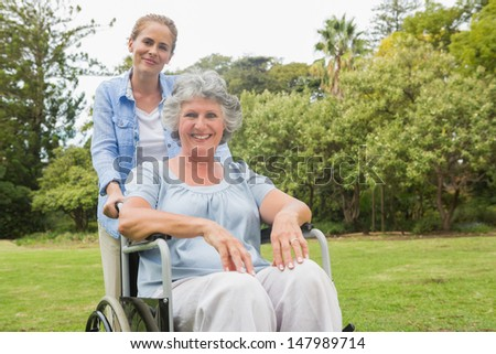 Woman in wheelchair with her daughter smiling at camera in the park - stock photo
