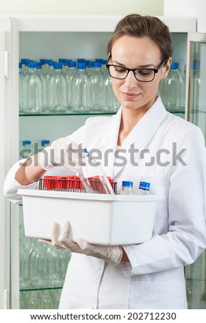 Woman in white apron holding box with laboratory equipment - stock photo