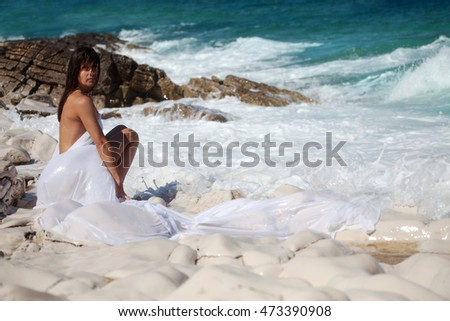 Woman in white cape dress relax on the rocky beach