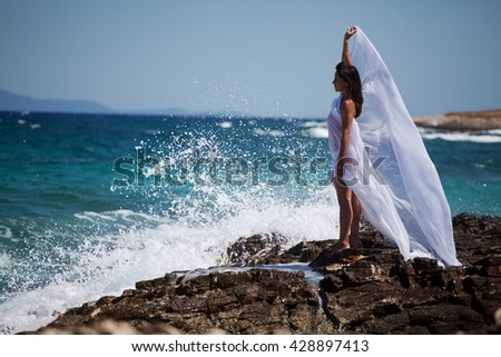 Woman in white cape dress stands on the rocky beach on the sea
