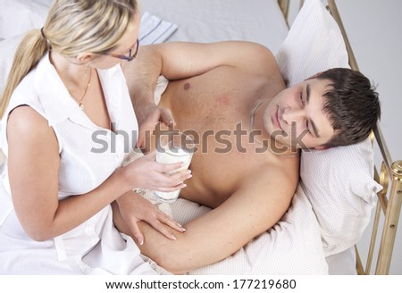 Woman in white coat caring sick man with a milk - stock photo