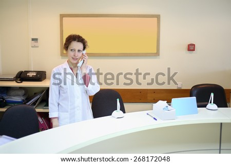 Woman in white coat talking on the phone at the reception - stock photo