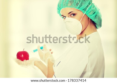 Woman in white coat with syringe and apple (biotechnologist). White background.  - stock photo