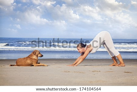 Woman in white costume doing Yoga and looking at the dog on the beach near the ocean in India - stock photo