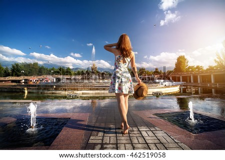 Woman in white dress and hat going bare foot to the fountain in the park in Almaty, Kazakhstan