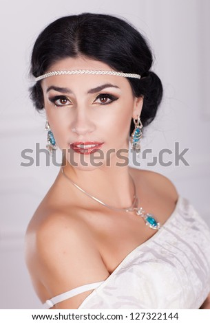 Woman in white dress - bride with bright makeup and fashion greek hairstyle in wedding dress and jewelry waiting for groom at home. stylish girl in vintage dress have final preparation for wedding