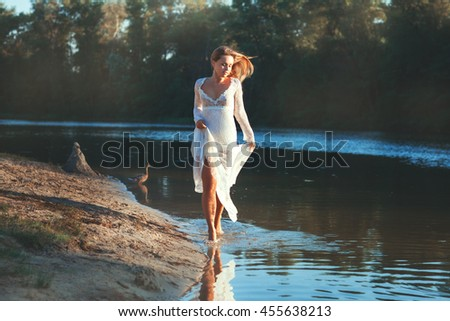 Woman in white dress running through the water of the lake.