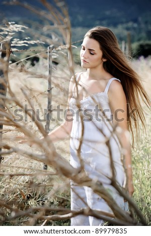 Woman in white dress stands alone in a field, fashion ethereal lonely concept.
