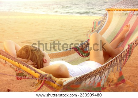 Woman in white dress sunbathing in hammock under bright sun on the beach - stock photo