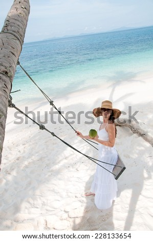 Woman in white dress swinging at tropical beach