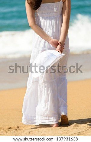 Woman in white dress walking on beach towards the sea. Vacation and leisure on coast in summer. - stock photo