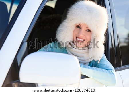 woman in white fur hat in a car smiling to you.