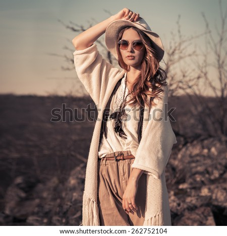 Woman in white hat and sunglasses posing outdoors - stock photo