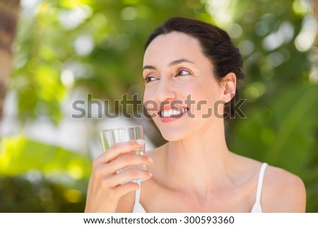 woman in white having a glass of water on a sunny day - stock photo