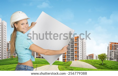 Woman in white helmet holds in hands white paper. Looking at camera, smiling. Green hills with road and buildings on background - stock photo
