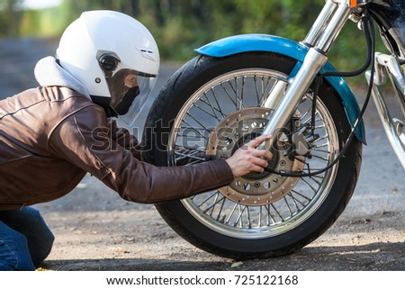 Woman in white helmet sitting on the kneels on the ground against motorbike spoked wheel, holding axis, repairing works