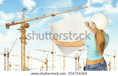 Woman in white helmet standing backwards and holding white paper sheet. Looks at paper. Tower cranes and blue sky in background - stock photo