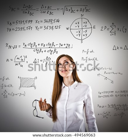 Woman in white is solving equation. Thinking.