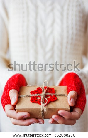 Woman in white knitted sweater and mitts holding a present. Gift is packed in craft paper with crocheted red snowflake. Example of DIY way to wrap a gift.