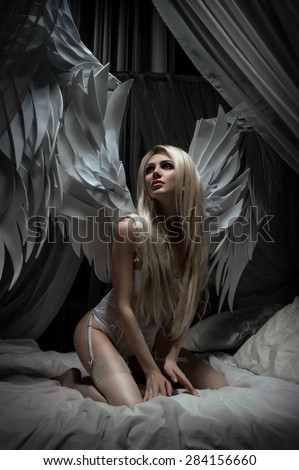 Woman in white lingerie with wings on bed - stock photo