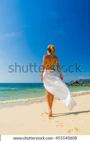 Woman in white sarong stepping on the beach on a bright day - stock photo