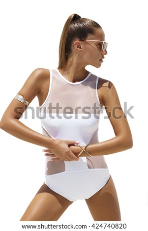 Woman in white swimsuit and golden sunglasses poses on isolated background. Fashion look - stock photo