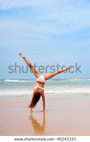 woman in white swimsuit doing cartwheel at the beach