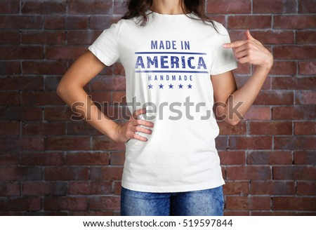 Woman in white t-shirt with text MADE IN AMERICA HANDMADE on brick wall background. Manufacturing quality concept.