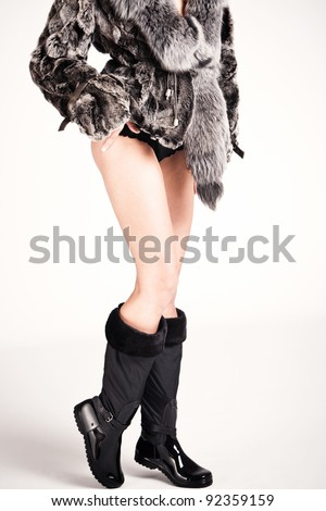 woman in winter boots and fur, studio shot - stock photo