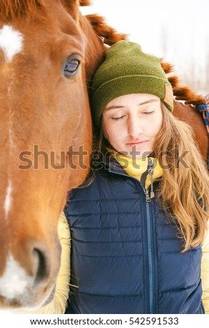Woman in winter clothes and the horse stand together against the white snow. love and care for horses. animal portrait on a white background.