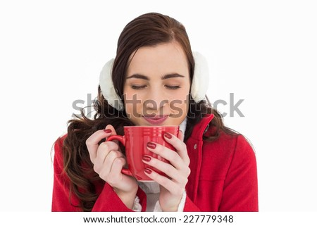 Woman in winter clothes enjoying a hot drink eyes closed on white background - stock photo