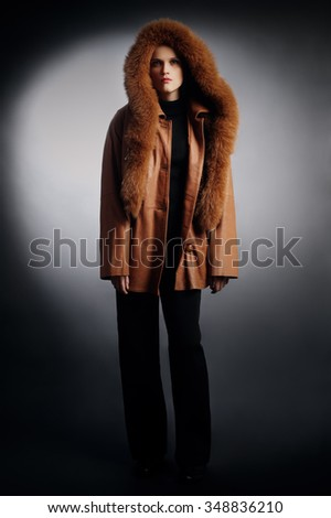 Woman in winter clothes fashion coat. Leather jacket with hood cowl - stock photo
