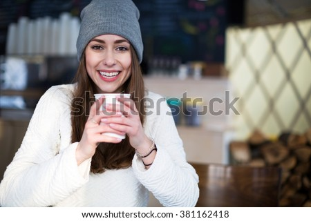 Woman in winter clothes having hot drink  - stock photo