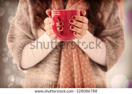 Woman in winter clothes holding a hot drink against autumnal leaf pattern - stock photo