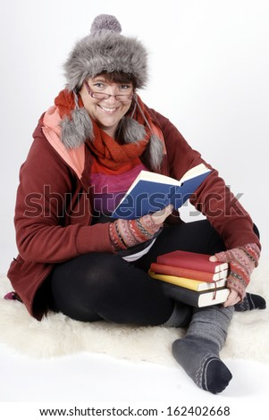 Woman in winter-clothes holding a stack of books and reading. - stock photo