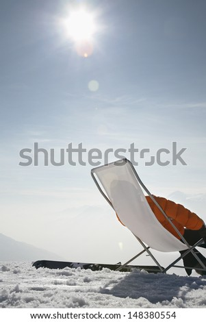 Woman in winter clothes relaxing on chair against sky